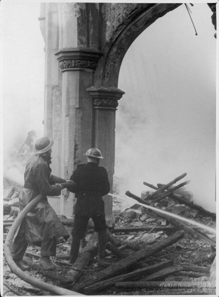 Firemen hosing down the remains of a London church