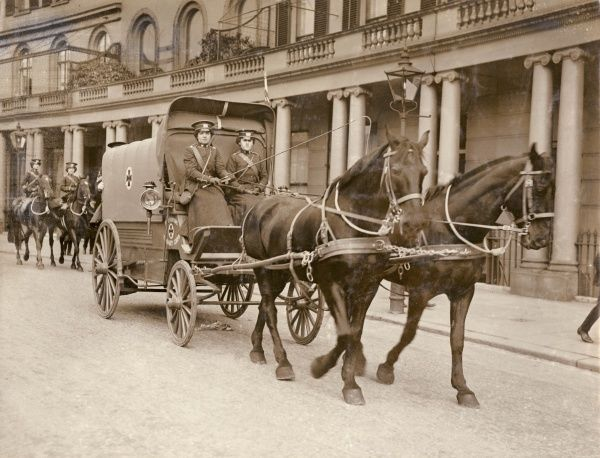 Two women of the First Aid Nursing Yeomanry (FANY) with their horse-drawn ambulance wagon