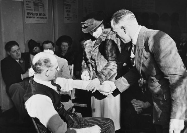 Special training in advanced first aid during World War II. A women is receiving instruction from Mr. Acres, Department Instructor