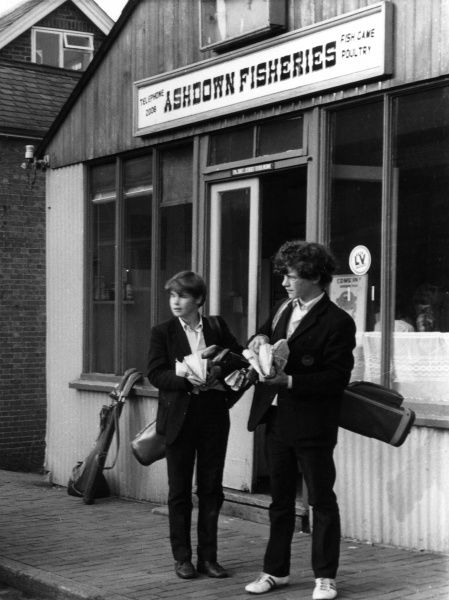Two teenage lads, still in their school uniforms, scoff down fish and chips wrapped in newspapers, after building up healthy appetites playing a round of golf after school. Date: 1967