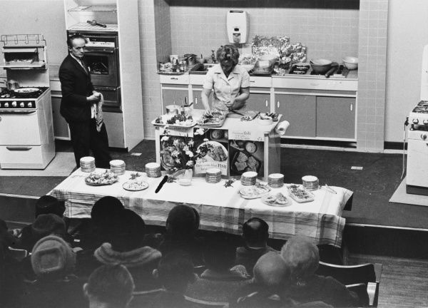 Ladies in fur coats watching a cookery class, possibly for television, where the cook is demonstrating the art of oven fried fish! Date: 1960s