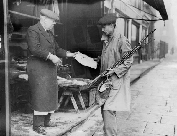 A fisherman stops off to buy his dinner after failing to catch anything Date: 1930s