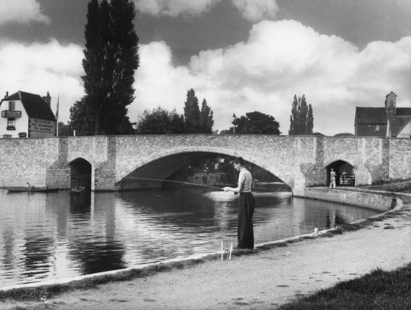 A young man stands fishing on the river bank at Abingdon, Berkshire, with its graceful bridge over the river Thames nearby