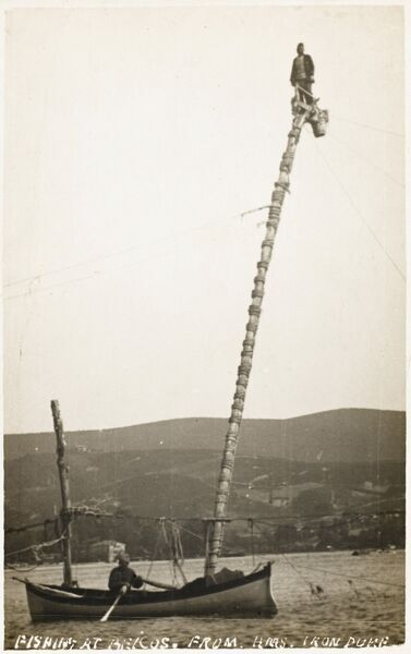 A photograph taken from the deck of the HMS Iron Duke of fishing at Beykoz (Beicos), Turkey. A fisherman is positioned atop a large pole, connecting sets of nets. A small rowing boat moves inside the array of nets