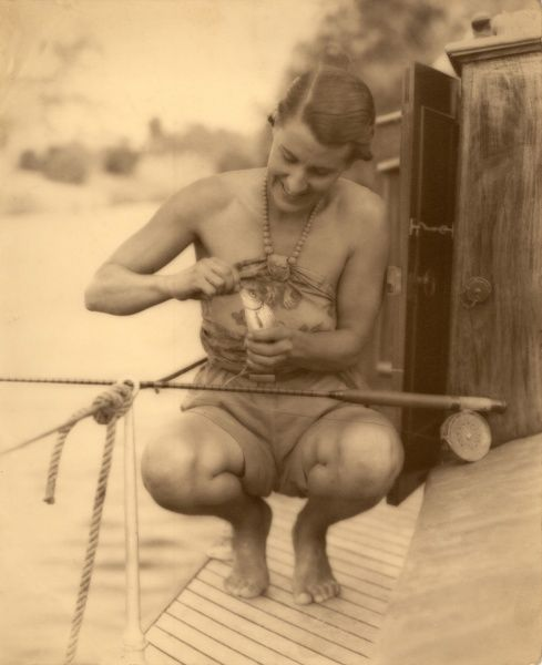 A woman looking very tribal in a halter neck top, shorts and bare feet unhooks a freshly caught fish on the deck of her boat, while on the Waveney River at Geldeston near Beccles in Norfolk, East Anglia