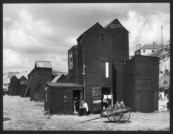 Clustered on the shingle of the old town of Hastings, Sussex, are these tall black huts, where the local fishermen dry and mend their nets