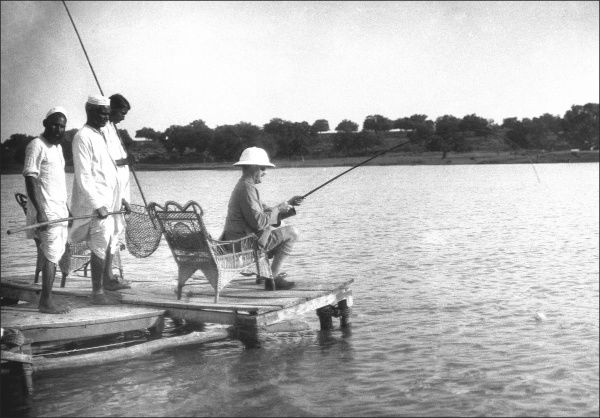 A wonderful photograph showing colonial life in India in the early 1920s. A British diplomatic service gentleman fishes from the comfort of a wicker chair by the banks of a wide Indian river, attended to by three staff armed with poles and nets