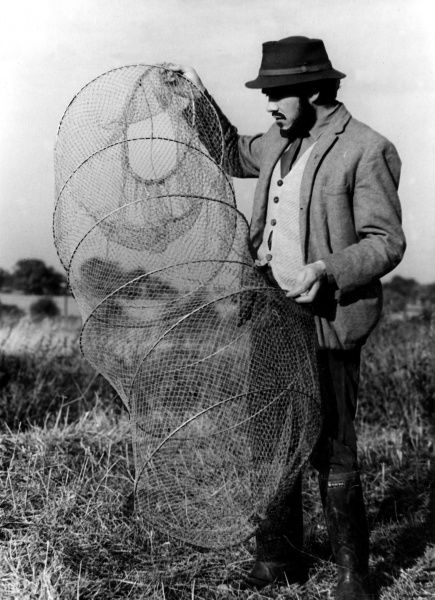 A man with a beard, wearing a 'pork pie' hat and wellington boots, holds up a fishing keepnet. Date: 1960s