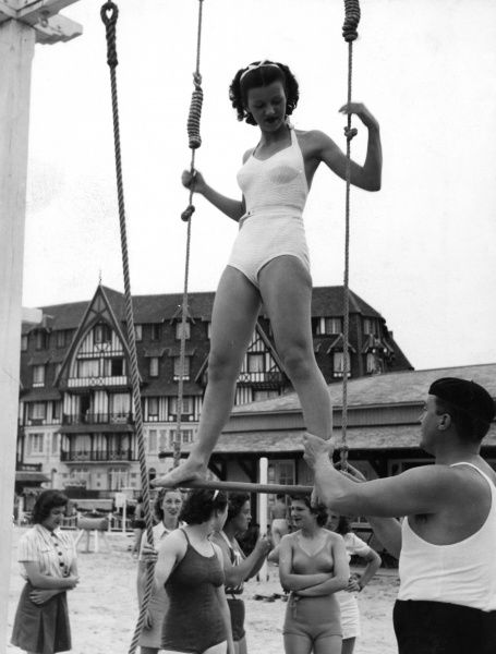 Girls exercising under the guidance of a fully trained instructor at the French coastal resort of Trouville, France, where a well-equipped gymnasium has been built on the beach by the local authorities