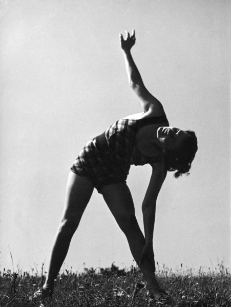 A side stretch, performed in the open air for added health benefit. Date: 1930s
