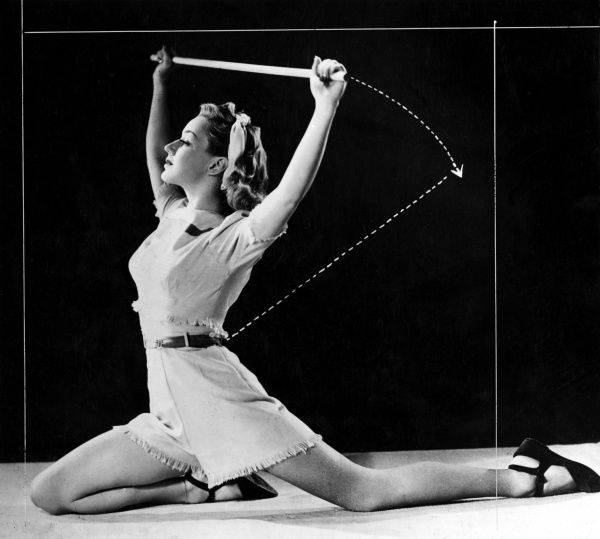 A woman performs a perfect stretch. Date: 1940s