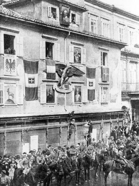 A street in Fiume (now Rijeka, Croatia) with flags draped on the buildings, and portraits of the King, Gabriele D'Annunzio and two generals, under Italian nationalist occupation. Date: 1919