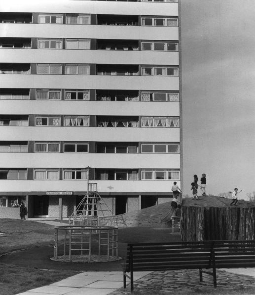 A block of flats on a council estate in Birmingham with a children's play area in the foreground Date: 1968