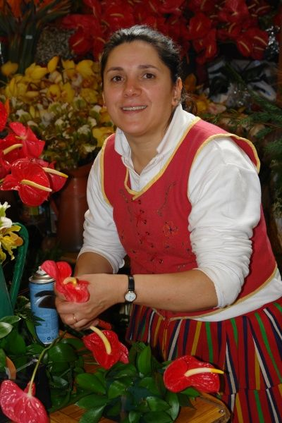 A woman in traditional costume in the flower market at the Mercado dos Lavradores (Workers' Market), Funchal, capital city of Madeira