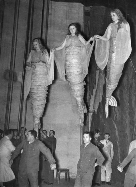 Flying mermaids! Mermaids suspended with wires, which are being operated by the men underneath them. Date: 1930s