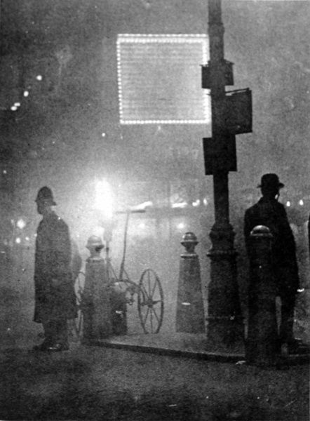 Photograph showing a Policeman (left) standing at a street refuge in Piccadilly Circus, London, during a heavy fog in December 1924. This image was taken at noon