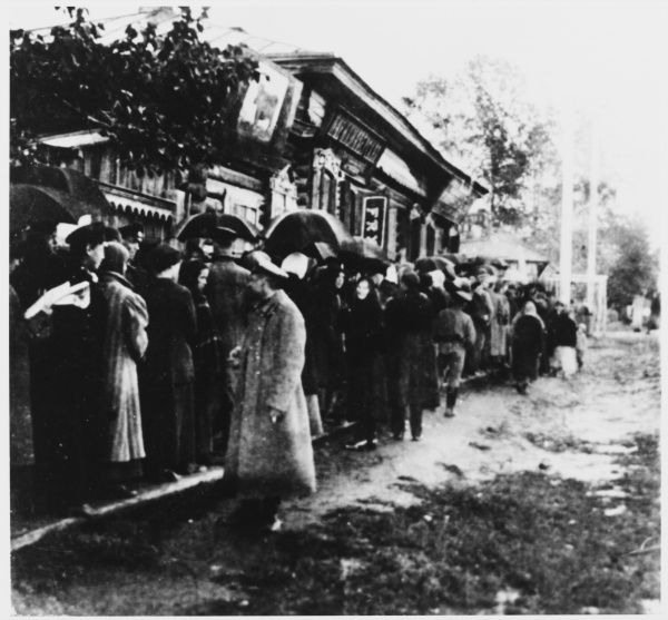 War and revolution combine to bring food shortages throughout Russia : residents of Tomsk, Siberia, queue for meat in the rain
