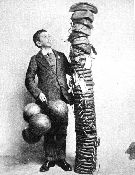 A boy in a suit admires a tower of uninflated footballs, some with labels attached, destined to be sent as wartime Christmas gifts to soldiers at the front in world war one