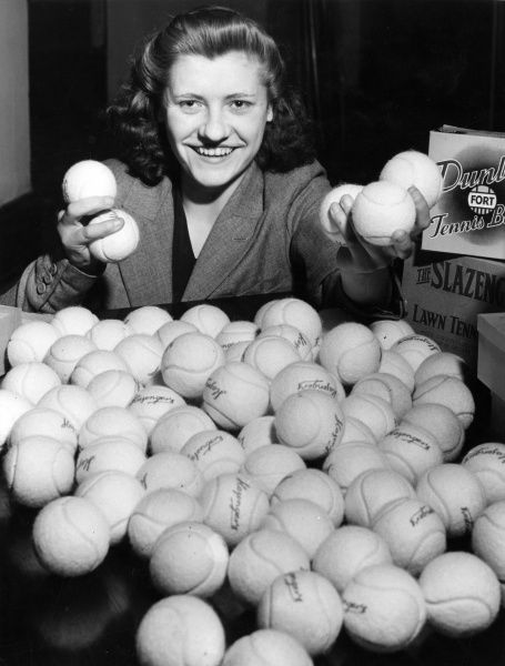 A Lillywhite's girl shows off the surplus of tennis balls donated by Dunlop, Slazenger etc. following an appeal due to a shortage within the Armed Forces! Date: 28 May 1942