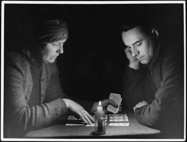 A fortune teller reads a man's fortune for him by candlelight, using a pack of ordinary playing cards