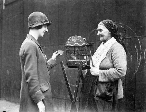 A young woman with a hooked nose, wearing a cloche hat, asks an old gipsy woman if her canary can tell her fortune. Date: early 1930s
