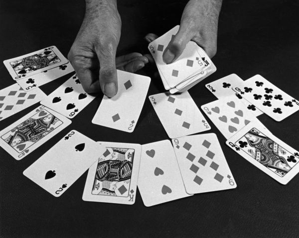 Fortune telling with an ordinary (not Tarot) pack of cards - dealing the cards. Date: 1960s