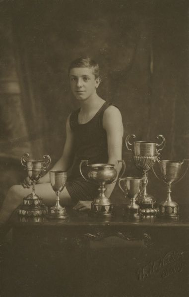 A 14-year-old swimming champion with the six trophies he has won. (2 of 2) Date: 1924