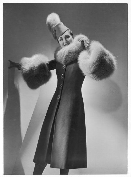 A grey three-quarter length coat with large buttons teamed with a brimless fez shaped hat by Jeanne Lanvin. Both are trimmed with grey fox fur