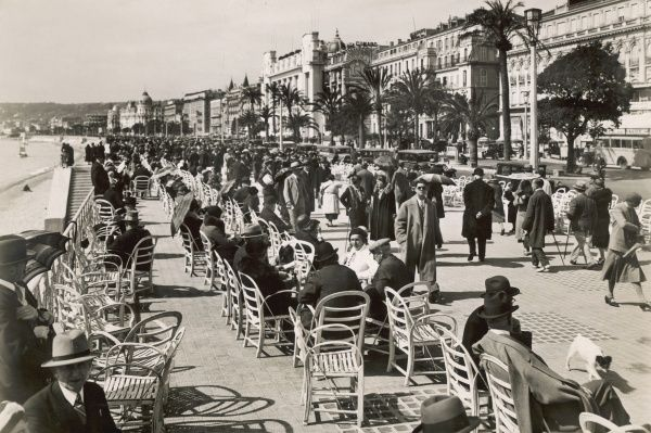 People enjoying a pleasant walk along the Promenade des Anglais, Nice, on a sunny January morning