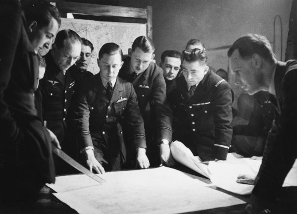 A group of French and British pilots study an operational chart during World War II