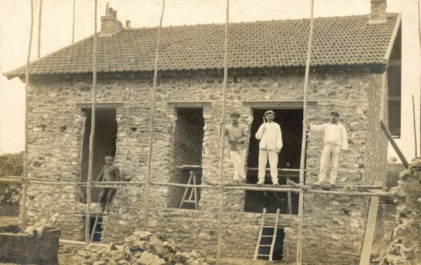 French builders at work on a stone-clad brick-built house, using some rudimentary wooden scaffolding