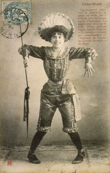 According to the caption, the cakewalk was invented by the kangaroo, but that doesn't explain this lady's eccentric cakewalking costume - and is that a spear she's holding ?