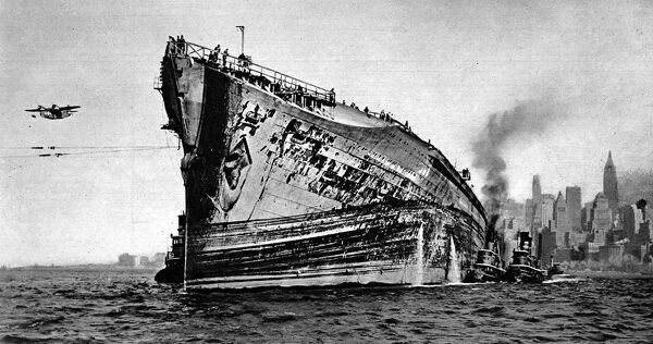 Photograph of the 'Normandie' in New York Harbour, November 1943. The 'Normandie' had just been refloated and was being towed to dry dock for repairs, after catching fire and capsizing in the harbour during 1942