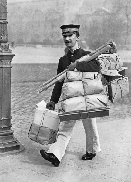 A busy parcel delivery man in Paris seen hard at work during the Christmas season. Attched to one of the big 'magasins' or department stores, he is loaded with parcels and packages up to his chin. Date: 1913