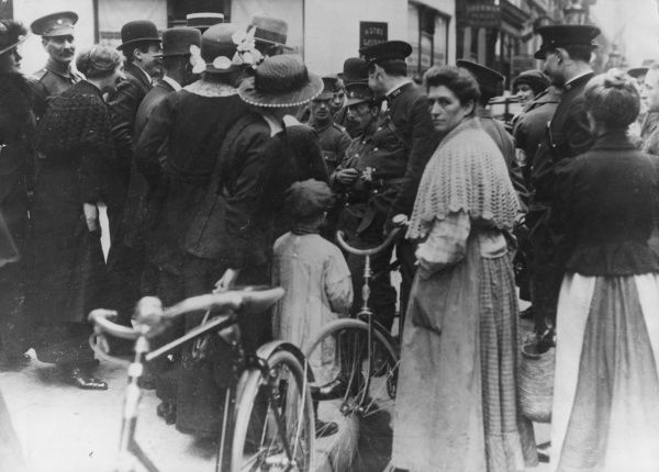 Scene in a French street during the First World War. A crowd of people, including a policeman, give directions to a British soldier who has lost his way. Date: 1914-1918