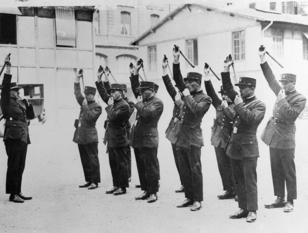 French police cadets with truncheons and whistles, being trained in self defence at a police school in Paris, France. Date: 1930s