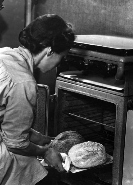 A housewife takes her two freshly home baked loaves, one white and one wholemeal. from a hot oven. Date: 1940s