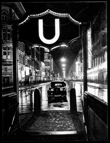 A deserted Friedrichstrasse by night, with illuminated U-Bahn sign framing the scene
