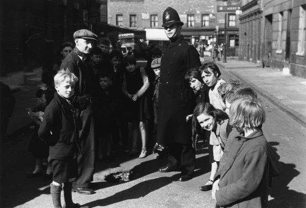 A friendly London policeman, standing in front of a hole in the road with a group of children and a working man in a flat cap