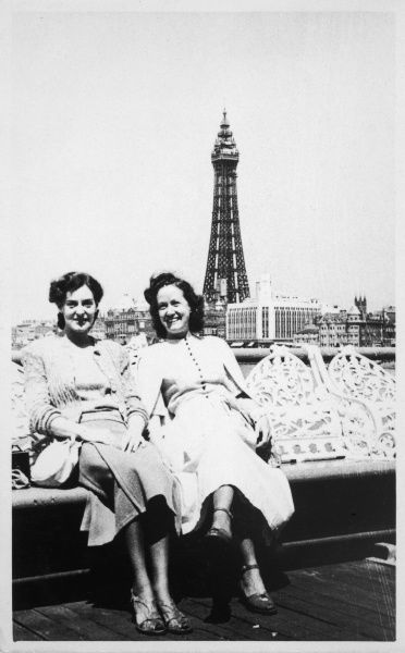 Two female friends rest on a bench with the Blackpool Tower in the background
