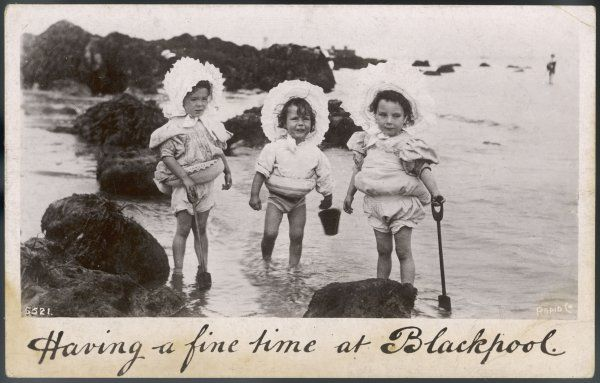 Three little girls at Blackpool keep their complexions fair by wearing large lacy broad brimmed bonnets which secure under the chin with a bow