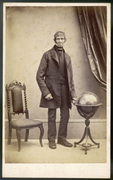 A very tall man, his hand resting on a globe, wears a frock coat, narrow trousers, a single-breasted waistcoat with no collar & a dark cravat