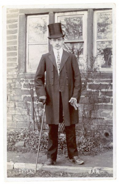 Young man in frock coat, high stand-fall shirt collar with rounded ends, slim patterned tie, pale coloured waistcoat, dark narrow trousers, top hat, cane & leather gloves