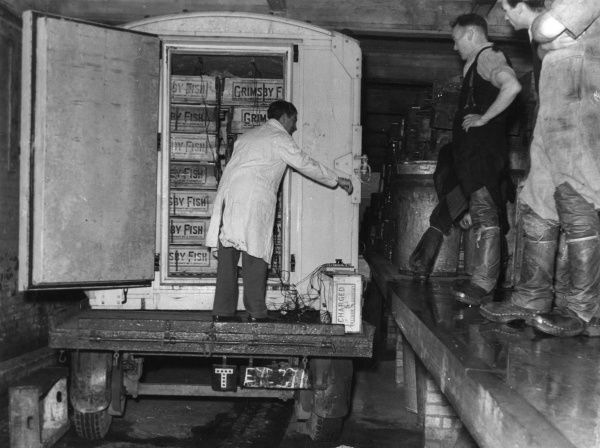 A member of the Ministry of Food, Scientific Advisor's Division, conducts a test on a railway container of quick frozen fish, etc., Grimsby, Lincolnshire, England. Date: 1950s