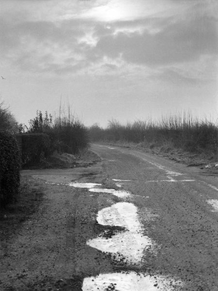 The hazards of a country lane in winter - frozen puddles. Date: 1960s