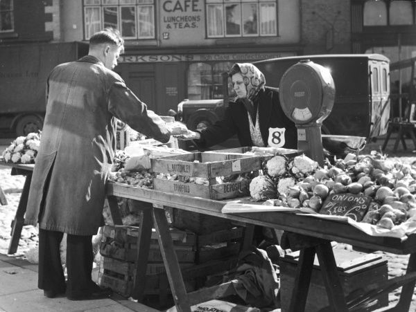 A rather serious transaction taking place on the fruit and vegetable stall at Knaresborough Market, Yorkshire, England, where 6d buys 3lbs of onions!