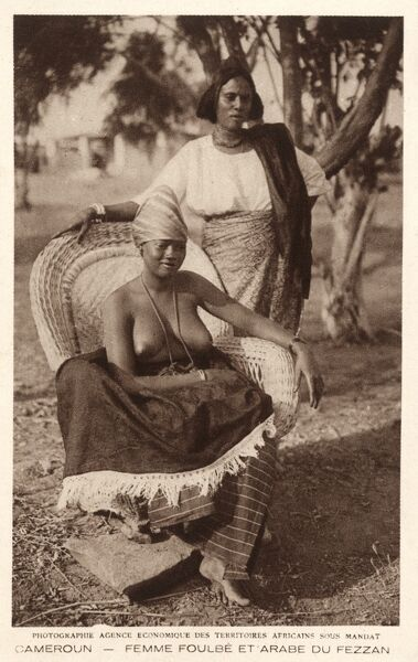 Cameroon, Africa - A seated bare-breasted Fulbe woman and a Fezzan bedouin arab woman from Southern Libya. Date: circa 1920s