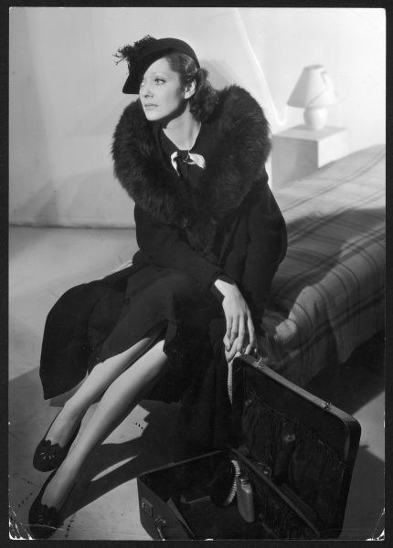 A stylish woman sits on the edge of a bed resting before she finishes her packing. She wears either a fur stole or a coat with a deep fur collar