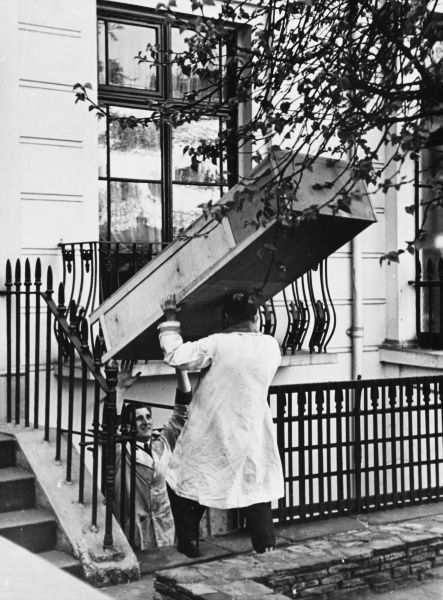 Furniture was collected from local residents during World War II. Here, a wardrobe is being brought from the basement of the Honourable Mildred Campbell's house in Chelea, London