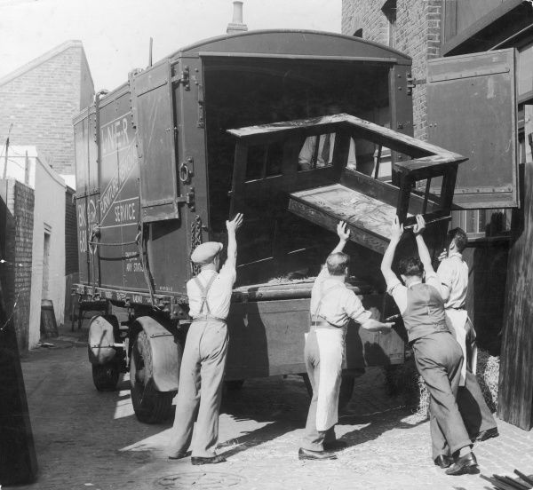 Four men load a large wooden window seat into the back of a L.N.E.R. (London & North Eastern Railway) furniture removal van